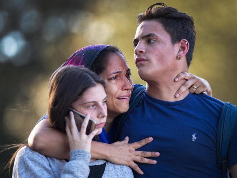 Überlebt: Eine Angehörige umarmt zwei Schüler der Marjory Stoneman Douglas High School nach den tödlichen Schüssen. Foto: Greg Lovett/Palm Beach Post via ZUMA Wire